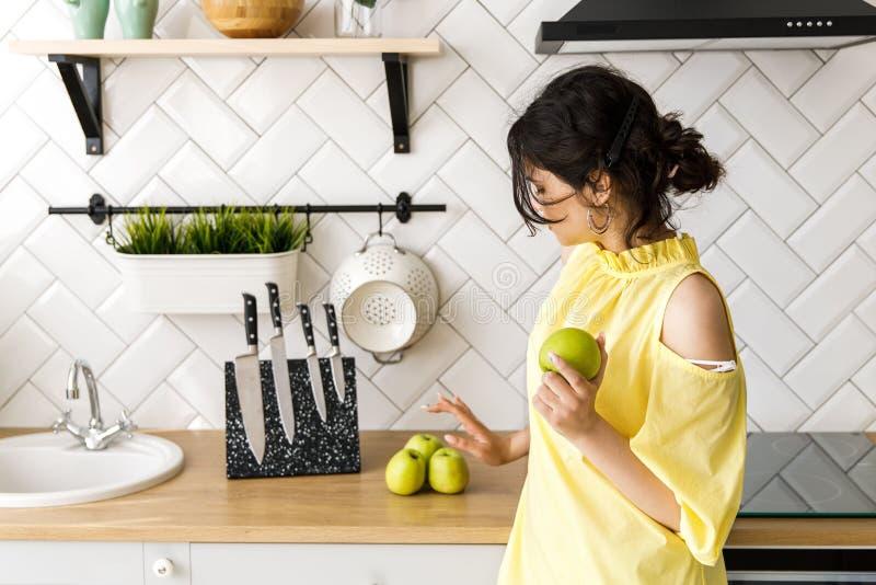 Den unga nätta flickan äter läckra saftiga gröna äpplen Hemtrevligt och ljust kök arkivfoton