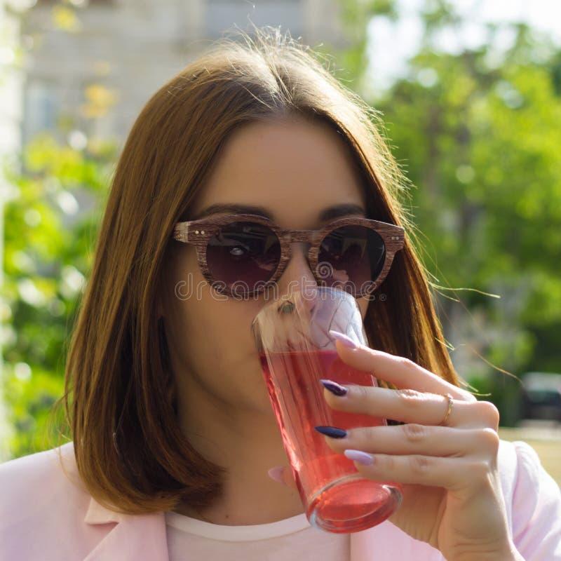 Den unga nätta flickan dricker en kall dryck som är utomhus- royaltyfri foto