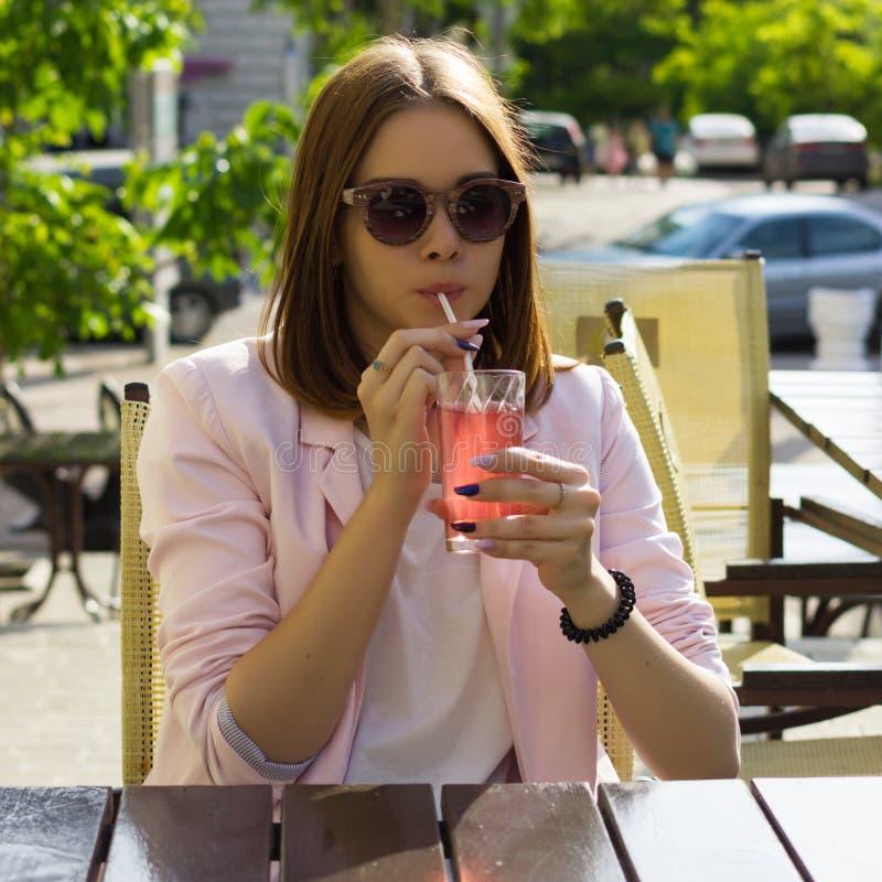 Den unga nätta flickan dricker en kall dryck som är utomhus- arkivfoton