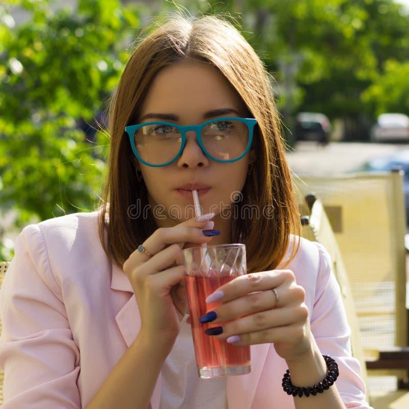 Den unga nätta flickan dricker en kall dryck som är utomhus- arkivfoto