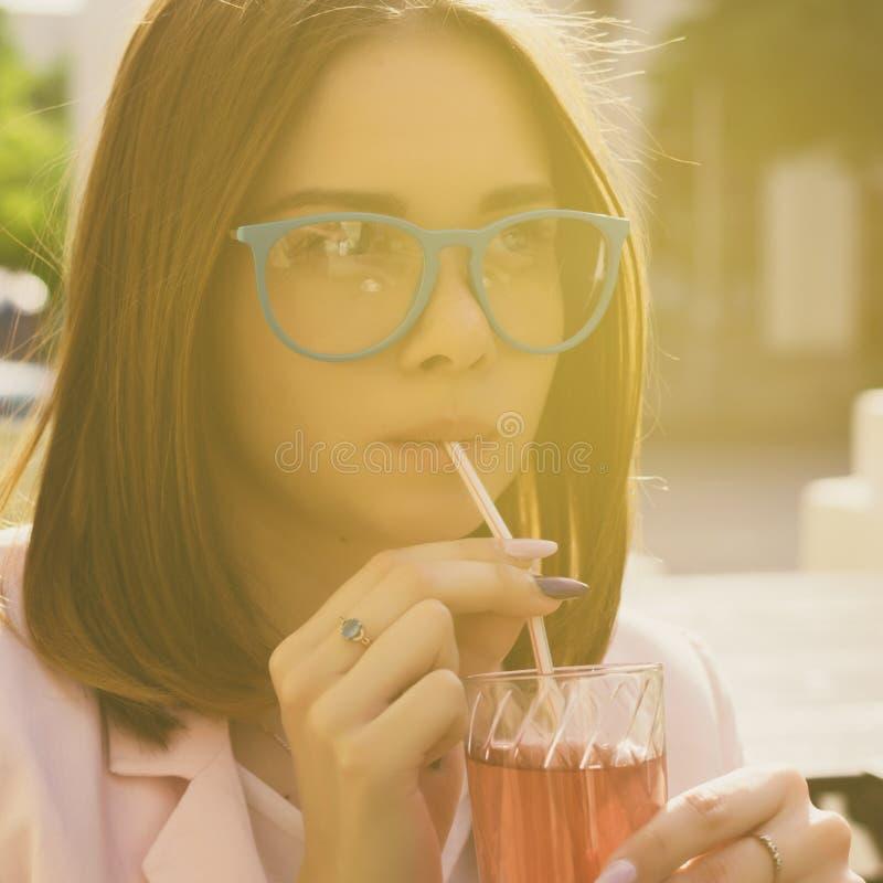 Den unga nätta flickan dricker en kall dryck som är utomhus- arkivbilder
