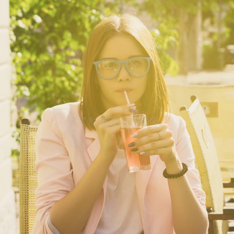 Den unga nätta flickan dricker en kall dryck som är utomhus- royaltyfri fotografi