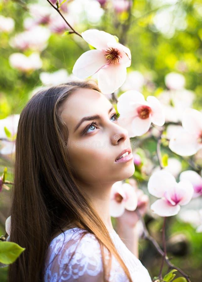 Den unga nätta flickan kopplar av i härlig trädgård Fantastiska rosa magnolior royaltyfria bilder
