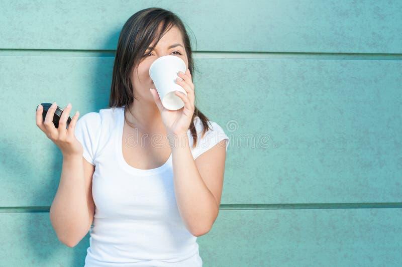 Den unga nätta flickan som dricker från takeaway kaffe, rånar royaltyfri foto