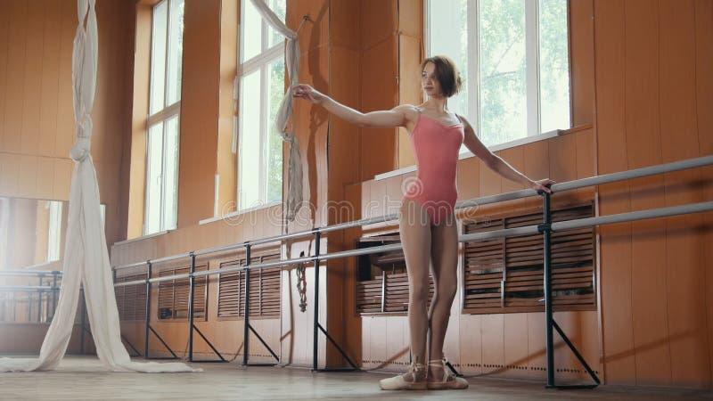Den unga nätta flickan visar böjligheten av hennes kropp royaltyfri foto