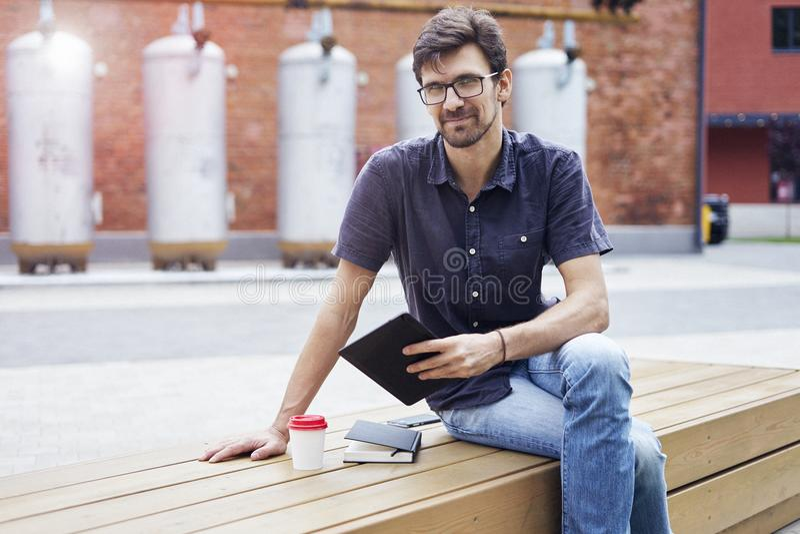 Den unga nätta grabben i exponeringsglasarbete utanför i parkerar genom att använda den moderna minnestavlan, anteckningsboken, m royaltyfri fotografi