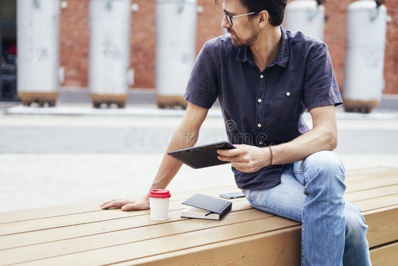 Den unga nätta grabben i exponeringsglasarbete utanför i parkerar genom att använda den moderna minnestavlan, anteckningsboken, m royaltyfria bilder