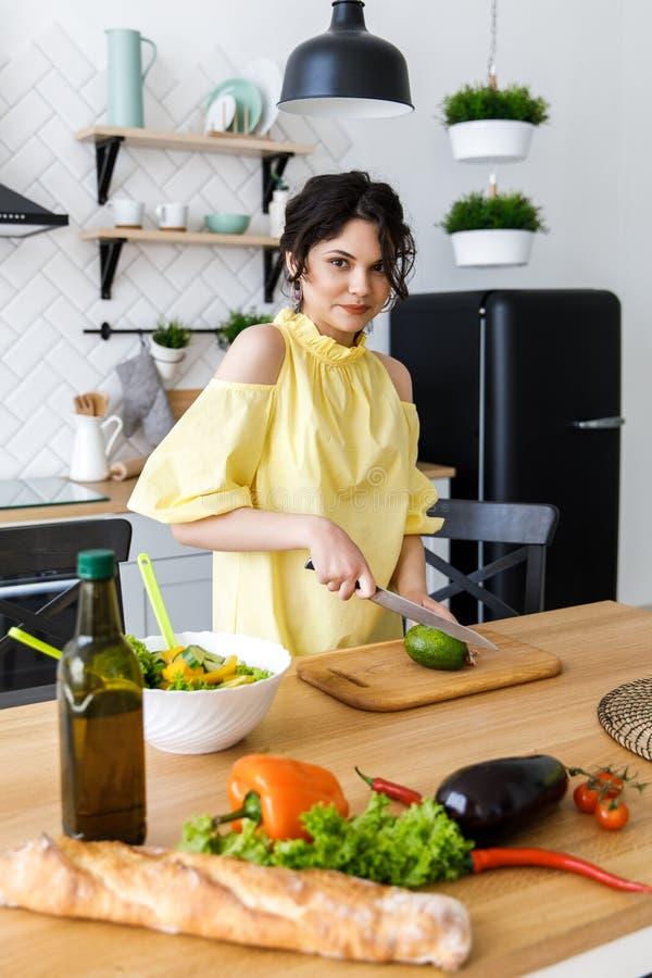 Den unga nätta kvinnan klipper en avokado på ett träsalladbräde matlagning Förberedelse av sallad för ny grönsak arkivfoto