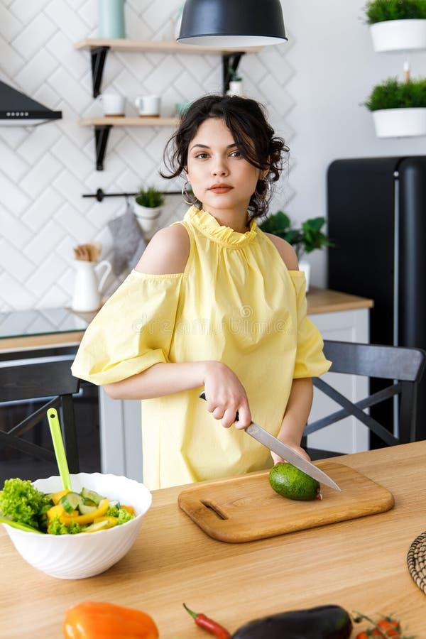 Den unga nätta kvinnan klipper en avokado på ett träsalladbräde matlagning Förberedelse av sallad för ny grönsak arkivbilder