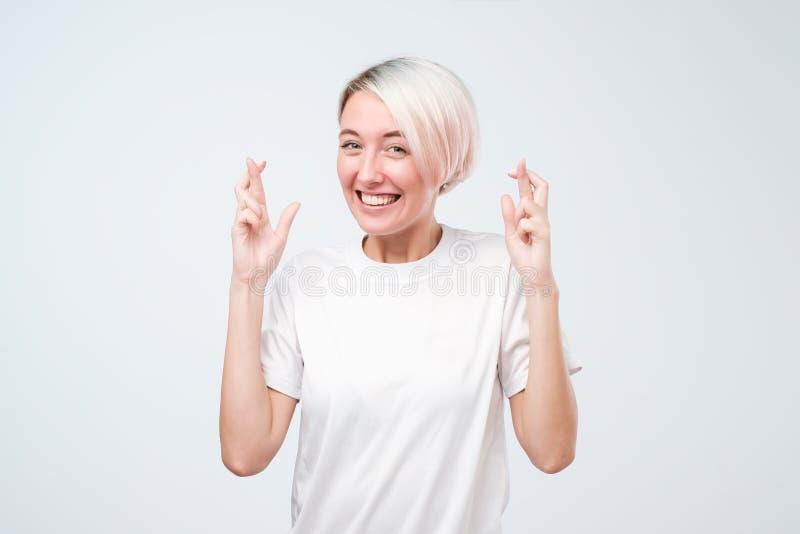 Den unga nätta kvinnan med färgat hår som gör en önska, korsade henne fingrar, lycka, stängda ögon, hoppfull gest arkivbild