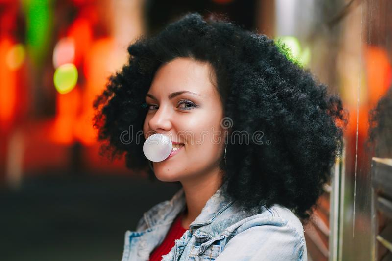 Den unga nätta kvinnan med mycket lockigt afro hår blåser upp en bubblaboll av vitt tuggummi på natten Moderiktig flicka som har royaltyfri fotografi