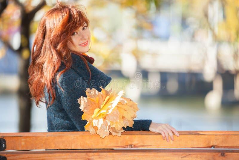 Den unga nätta kvinnan med rött hår som kopplar av i hösten, parkerar royaltyfria bilder