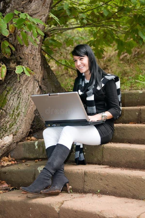 Den unga nätta kvinnan på hösten parkerar med datoren royaltyfria bilder