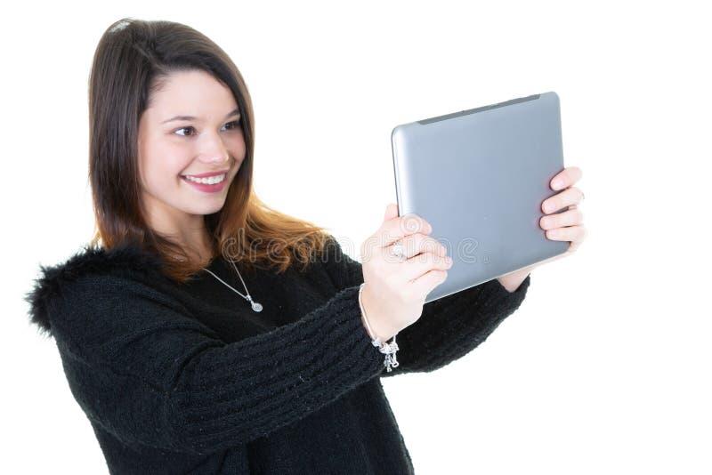 Den unga nätta kvinnan tar selfiefotoet med den digitala minnestavlan arkivfoto