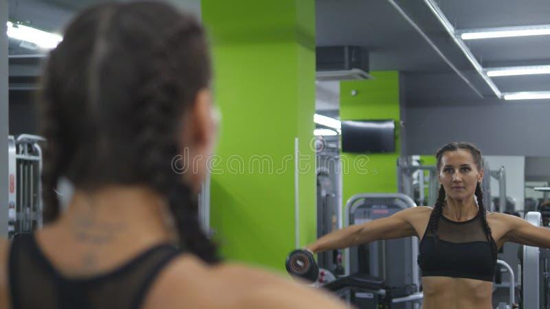 Den unga nätta kvinnan utbildar i idrottshallen som framme lyfter och fäller ned hantlar av spegeln Sportkonditionflicka royaltyfri bild
