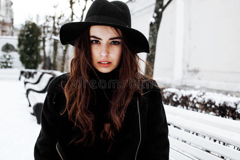Den unga nätta moderna hipsterflickan som väntar på bänk på vintersnö, parkerar bara, livsstilfolkbegreppet arkivfoton