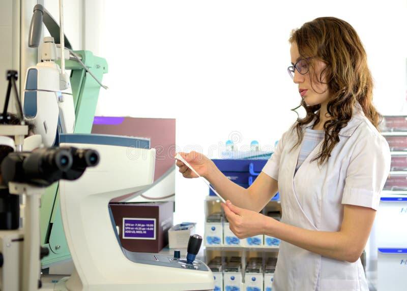 Den unga nätta optiker för kvinnaögonläkareoptometrikern undersöker visuell skärpa av en patient royaltyfri fotografi