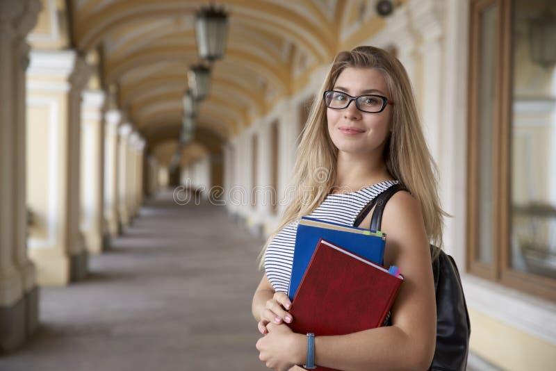 Den unga nätta studentflickan med långa hår och exponeringsglas rymmer i mummel royaltyfri bild