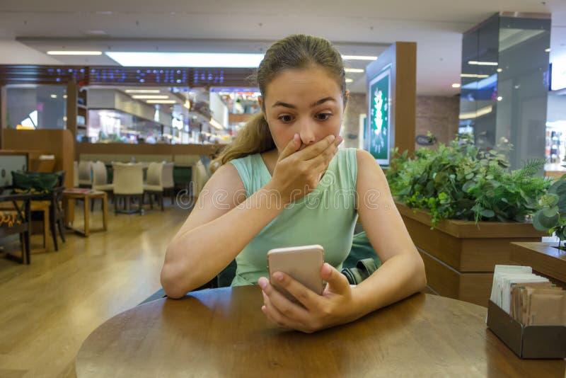 Den unga nätta tonåriga flickan läser chockerande nyheterna i hennes telefon arkivfoton