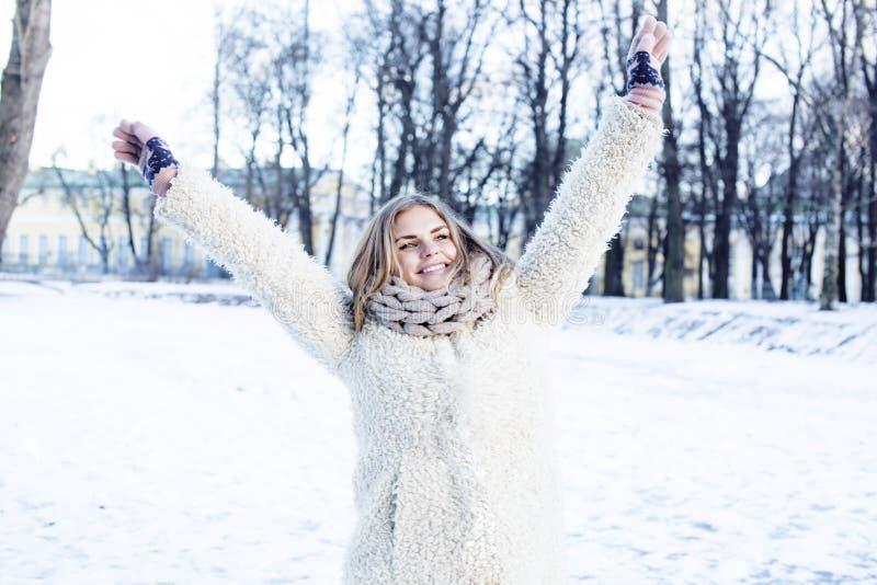 Den unga nätta tonårs- hipsterflickan som är utomhus- i vintersnö, parkerar att ha roligt dricka kaffe som värmer lyckligt le upp royaltyfria foton