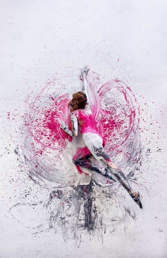 Den unga nakna kvinnan i rosa grå vit, färg som målas, ligger dansen på golvet som elegantly är dekorativt, i grå och vit färg arkivbild