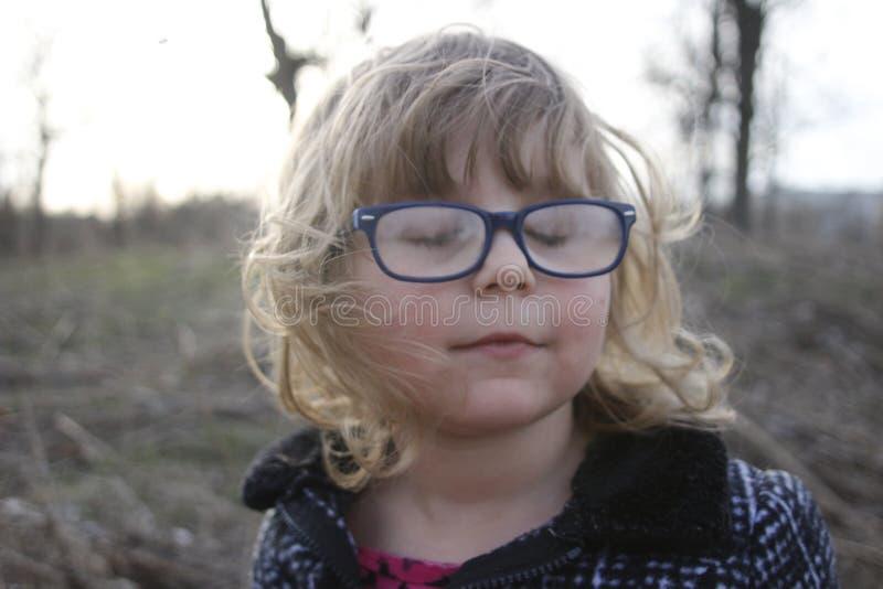 Den unga nerdy flickan med exponeringsglas åldrades 3-5, blont hår, blåa ögon Förskolebarnstående fotografering för bildbyråer