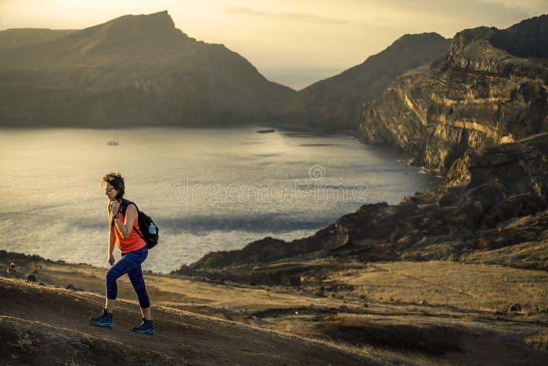 Den unga och attraktiva flickan i orange skjorta och blå damasker fotvandrar vid turistens slinga royaltyfri bild