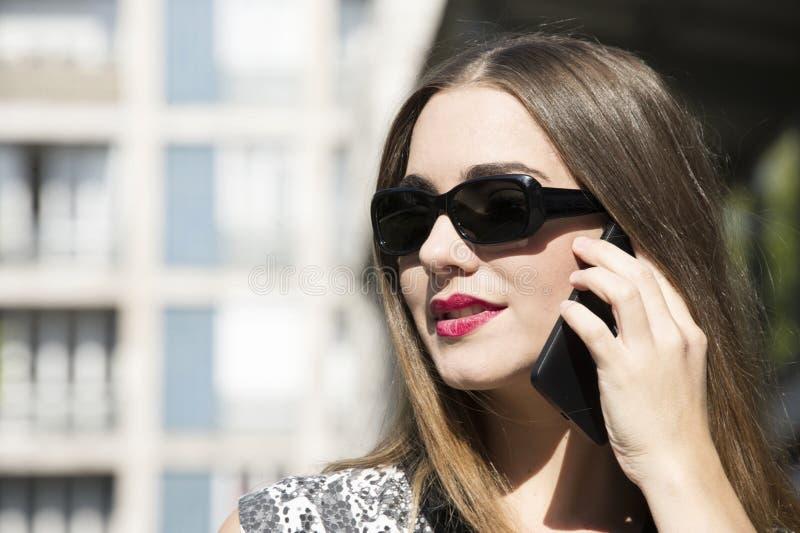 Den unga och attraktiva hipsterkvinnan talar på hennes mobil med en framsida som är full av sinnesrörelser arkivbild