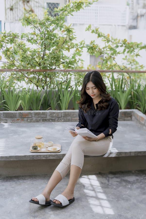 Den unga och h?rliga flickan sitter p? ett golv i sommarterrassen, l?ser en bok och dricker te arkivfoton