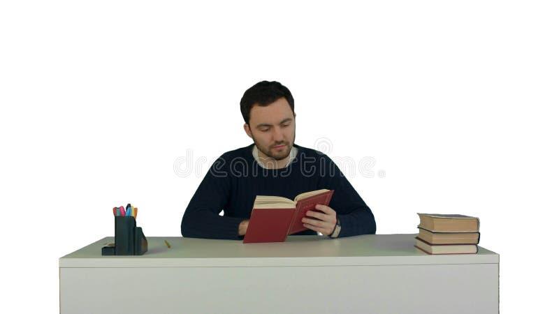 Den unga och koncentrerade studenten läser en bok på isolerad vit bakgrund fotografering för bildbyråer
