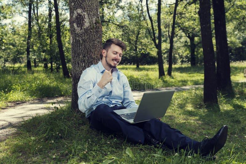 Den unga och lyckliga affärsmannen som sitter på en jordning med bärbara datorn i, parkerar och gör en lyckad gest arkivfoton
