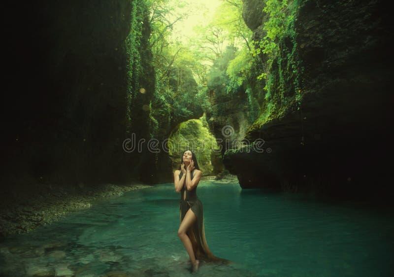Den unga och sexiga nymfen går i kanjonen bli i solljusen spela med turkosvatten wearig ett långt arkivbild