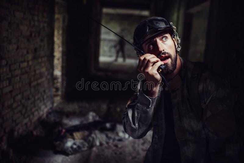 Den unga och skäggiga krigaren talar till den bärbara radion Också ser han upp En av soldater ligger på golvet royaltyfria foton