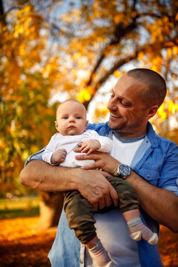 Den unga pappan som spelar med hans litet, behandla som ett barn sonen på varm au för solsken royaltyfri fotografi