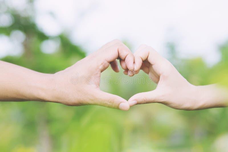 Den unga parvänshowen som rymmer händer, gör hjärta arkivfoto