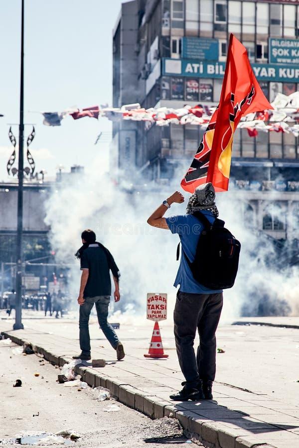 Den unga personen som protesterar som rymmer en flagga som kämpar mot tårgasen som avfyras av polisen under Gezi, parkerar protes arkivfoto