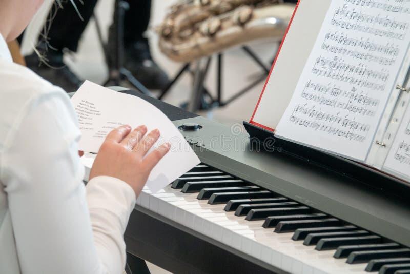 Den unga pianisten studerar schemat f?r en kapacitet arkivfoto