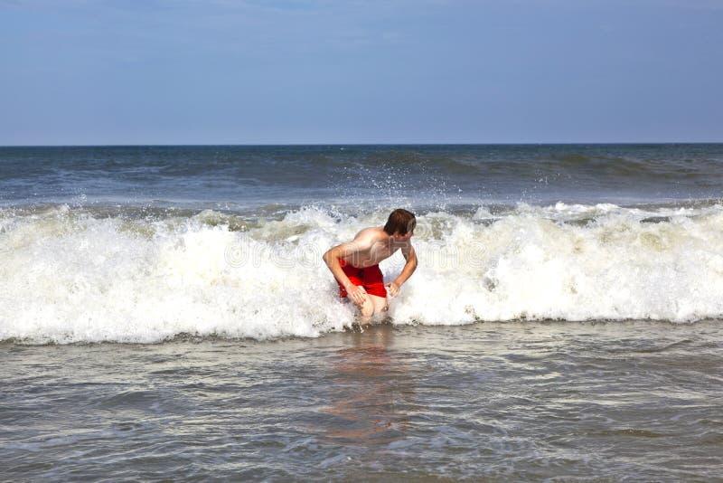 Den unga pojken är kroppen som surfar i vågorna royaltyfri fotografi