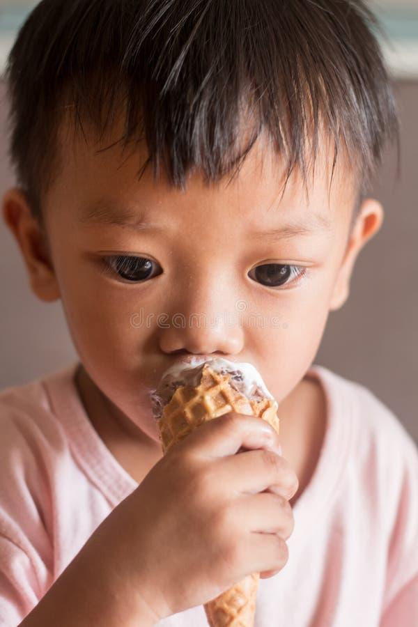 Den unga pojken äter glassframsidanärbild royaltyfri fotografi