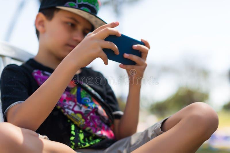 Den unga pojken bara som spelar med smartphonen i, parkerar arkivfoton