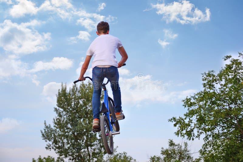 Den unga pojken hoppar med mountainbiket utan hjälmen fotografering för bildbyråer
