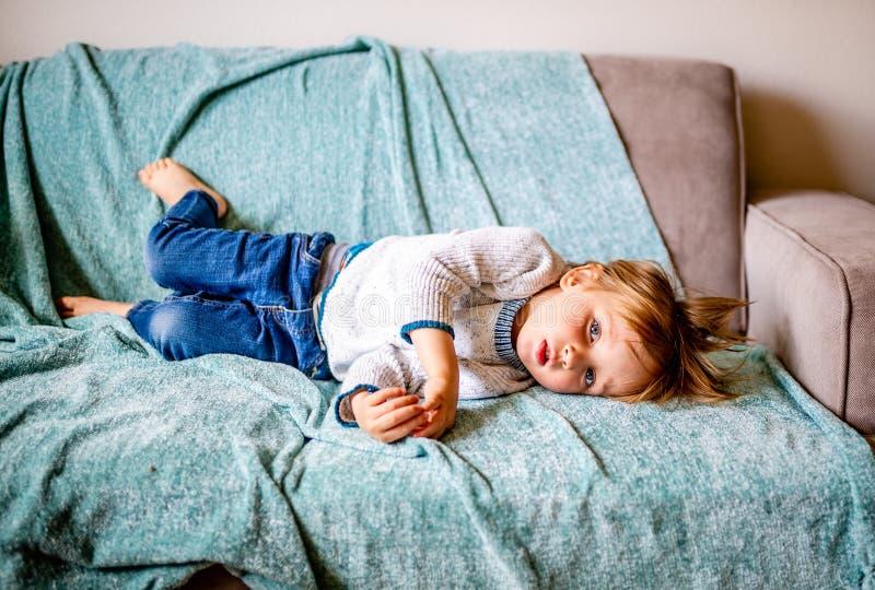 Den unga pojken lägger på soffan royaltyfria bilder