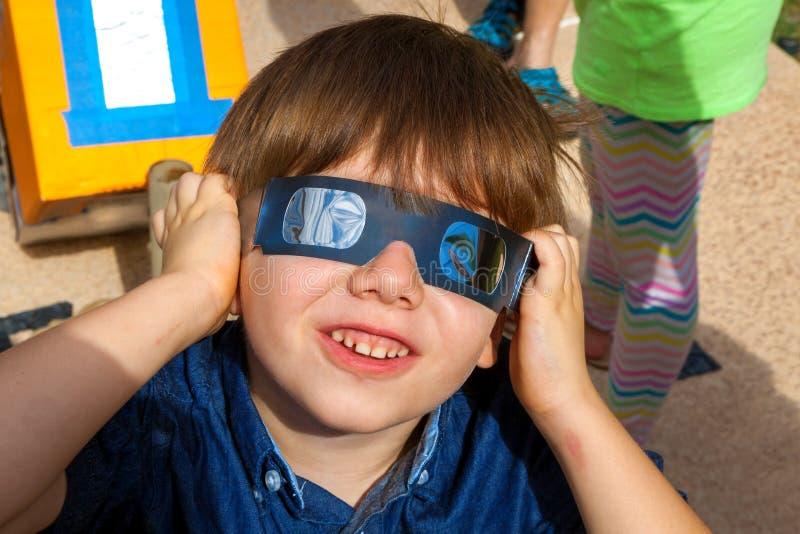 Den unga pojken med exponeringsglas för den sol- förmörkelsen ser upp på himlen som royaltyfria bilder