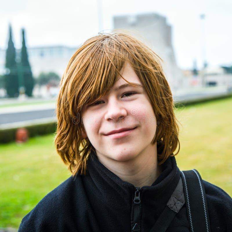 Den unga pojken med rött hår ler royaltyfri bild