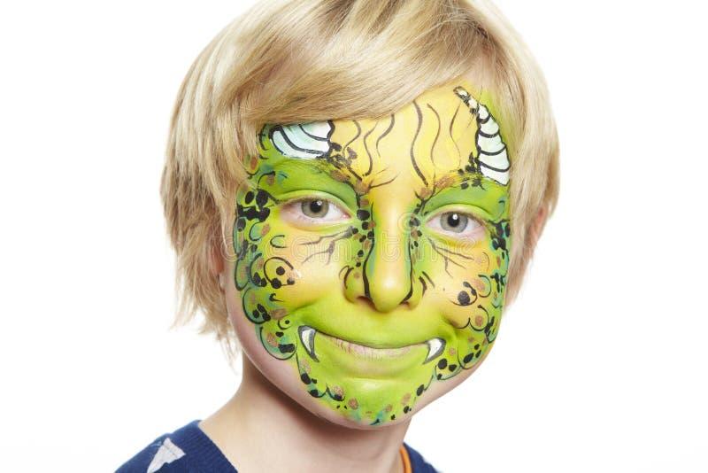 Den unga pojken med vänder mot målningmonster fotografering för bildbyråer