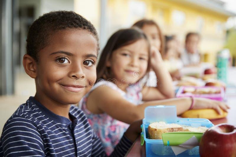 Den unga pojken och flickan på skolalunch bordlägger att le till kameran arkivbild