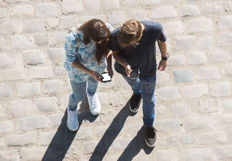 Den unga pojken och flickan ser mobiltelefon n gatan royaltyfria bilder