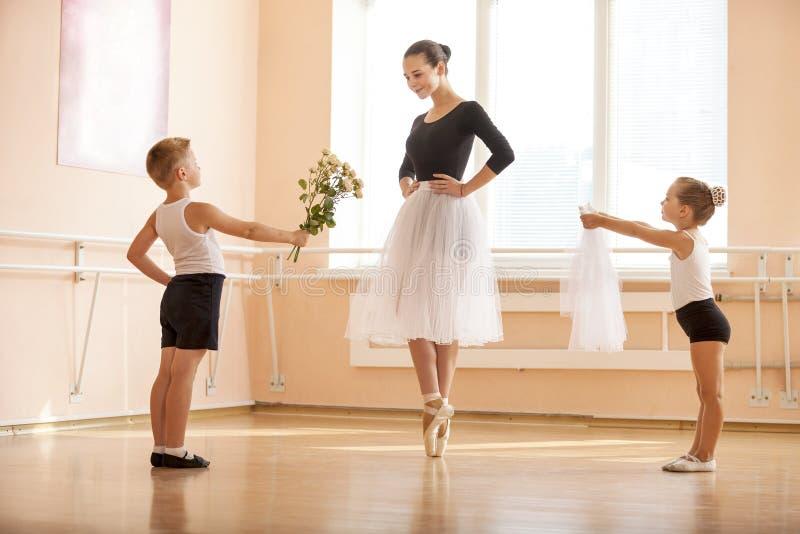 Den unga pojken och flickan som ger blommor och, skyler till äldre student, medan hon dansar en-pointe royaltyfri fotografi