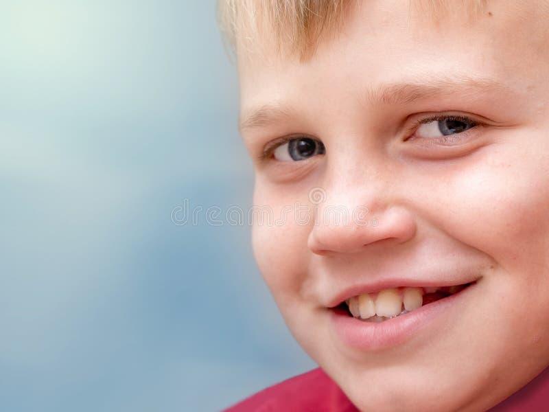 Den unga pojken på en oskarp blå bakgrund ler gulligt, vänstersidautrymme fo arkivfoton
