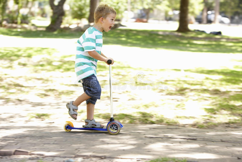 Den unga pojken på sparkcykeln parkerar in royaltyfri foto